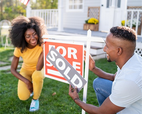 Two people putting a sold sign over a for sale sign at a house