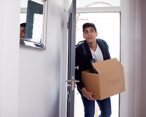 man carrying a box into a house